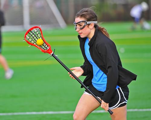 girl playing lacrosse while wearing eye safety googles
