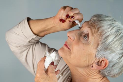 older woman putting in eyedrops